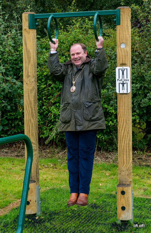 A man is laughing as he lifts himself off the ground using two green metal hoops above his head, suspended from a bar attached to wooden poles at either side