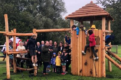 A crowd of adults and children stand in the rain, smiling, as a man prepares to cut a ribbon on wooden play equipment. Children stand on different parts of it, including a large tower to the right