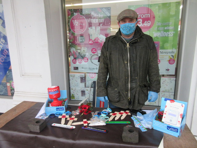 A man wearing a coat, hat and mask stands in a street behind a table on which are poppies and collection tins