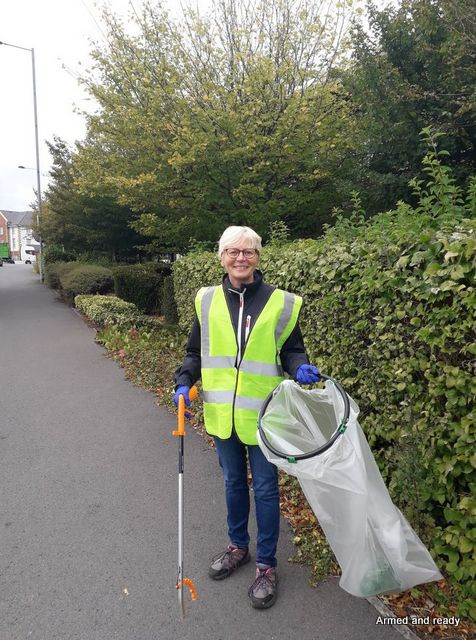 A woman wearing a hi viz tabard holds a litter picker and an empty rubbish sack