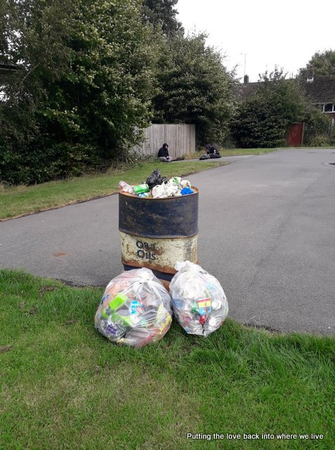 Two large sacks of litter sit in front of a metal drum, also full of litter