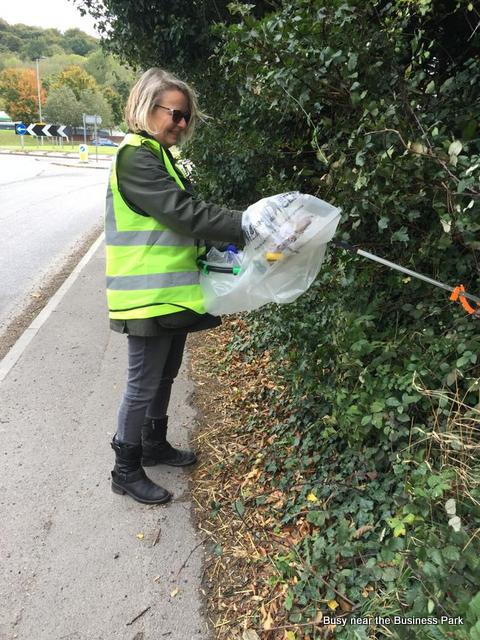 A woman clears litter from a hedge