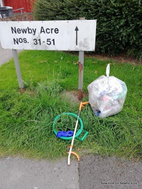 Litter equipment sits on the ground next to a road sign reading Newby Acre