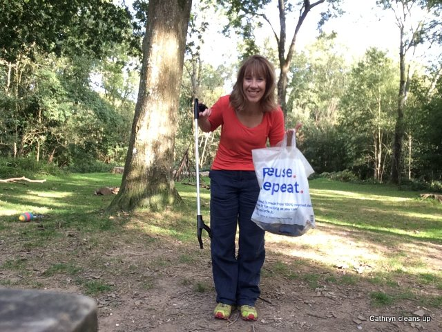 A smiling woman faces the camera. She holds a litter grabber in her right hand and a plastic bag full of rubbish in her left