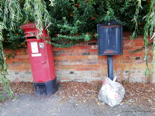 A pillar box, a plastic bag full of rubbish and a metal post are on a pavement with a brick wall behind