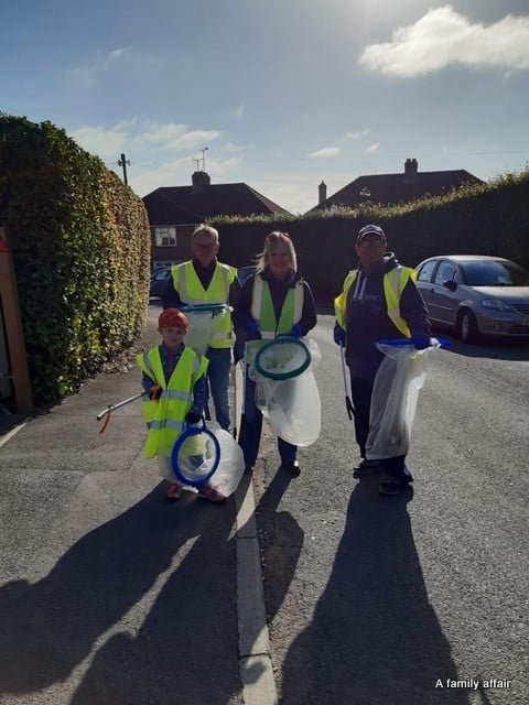 Two men, a woman and a young boy all wear hi visibility tabards and hold litter picking equipment. They stand in a street