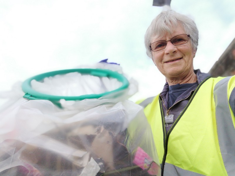 a woman wearing a hi viz vest smiles at the camera.  She is holding a large plastic bag full of litter