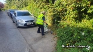 A woman with her back to the camera retrieves rubbish from the gutter of a lay by. Cars are parked behind her and there is a hedge to her right
