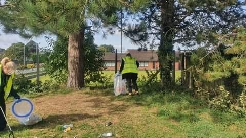 two people look down, picking up litter in a field