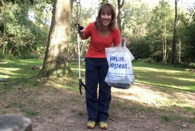 a woman stands on grass in a clearing between trees.  She holds litter picking equipment and smiles at the camera. This image is also a link to the full article