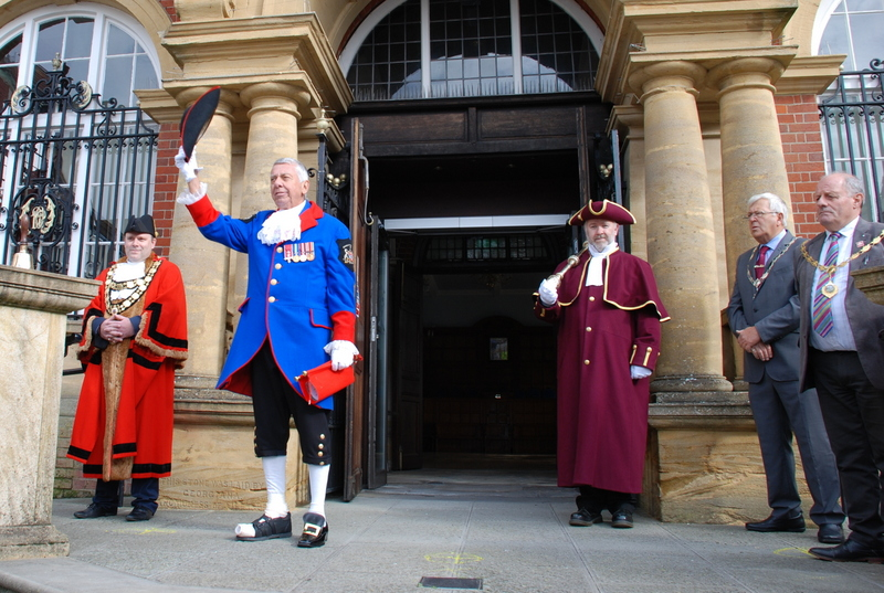 five men wearing robes or suits stand on steps in front of a building.  One man holds a tricorn hat above his head