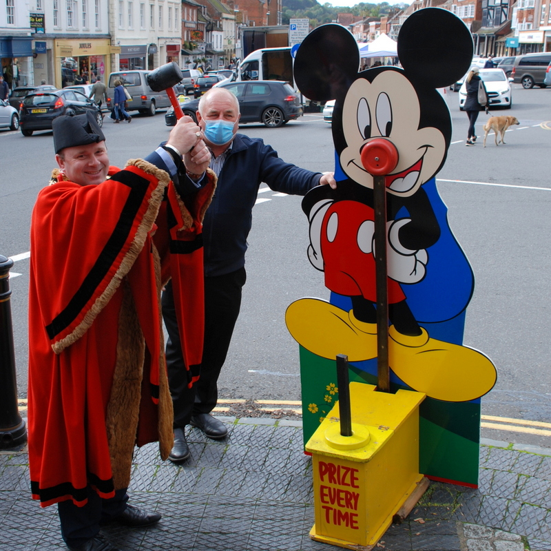 A man in a robe faces the camera, holding a mallet in both hands above his head. He is poised to strike a fairground attraction to ring a bell