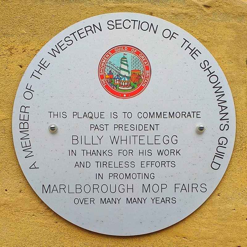 A round plaque containing text which gives thanks to Billy Whitelegg of the Showmen's Guild for his work and tireless efforts in promoting Marlborough Mop Fairs