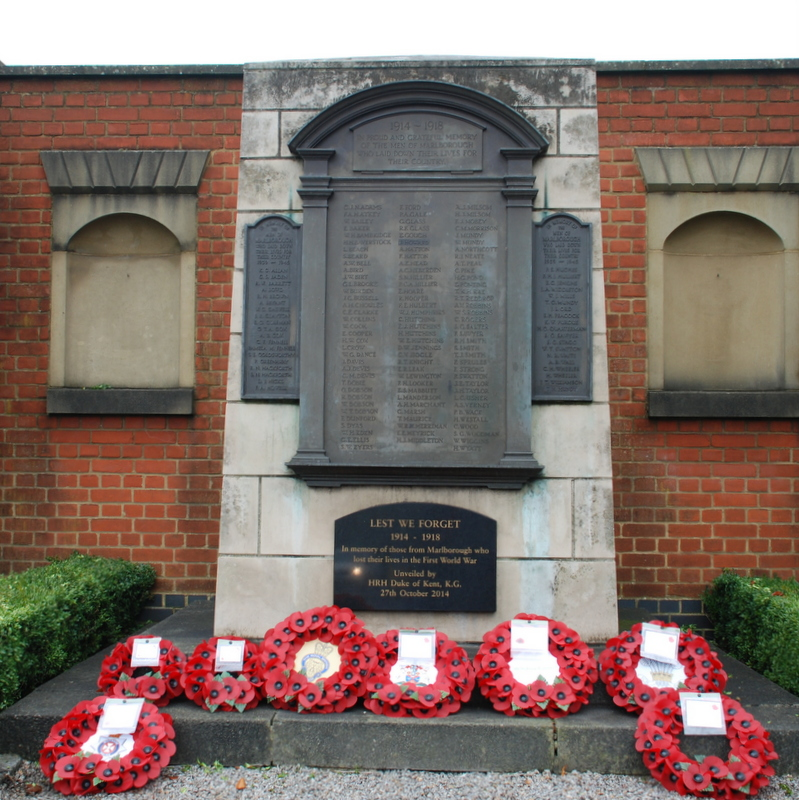 A number of poppy wreaths at the foot of a war memorial