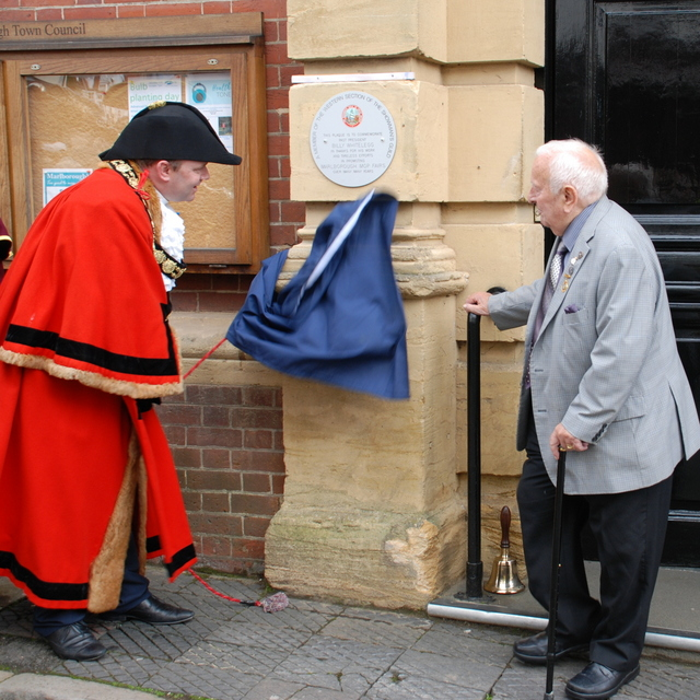 A man in a red robe pulls a curtain away from a wall to reveal a plaque. Another man stands to his right looking on