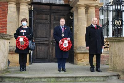 A woman and two men stand to attention .  Two hold wreaths of red flowers and one is speaking