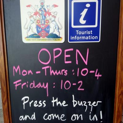 a black chalk board with a crest and a blue tourist information logo showing opening hours and the message press the buzzer and come on in