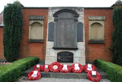 wreaths of poppies lie beneath a brick and stone cenotaph