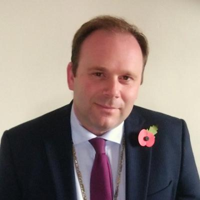 a head and shoulders photo of a man wearing a suit and tie with a poppy in his lapel