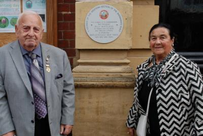 An elderly man wearing a jacket and tie faces the camera. On the right is a smartly dressed lady .  Between them on a wall there is a round plaque